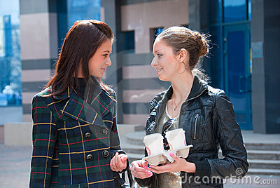 Two girls on a street with coffee