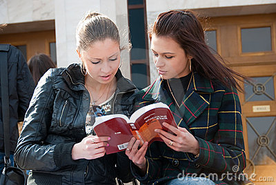 Two girls students read textbook outdoors