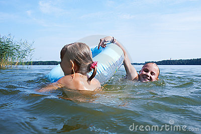 Two girls are swimming in a lake