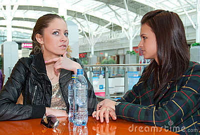 Two girls talking in food court in a mall