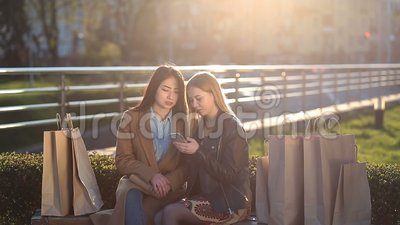 Two girls texting with friends in social network stock footage