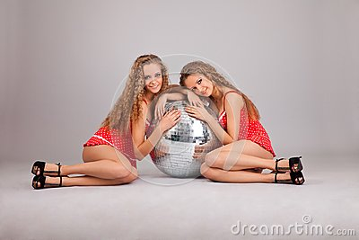 Two girls twins with glitterball on grey