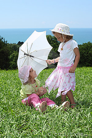 Two girls with an umbrella on lawn