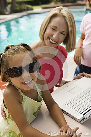 Two girls using laptop with grandmother