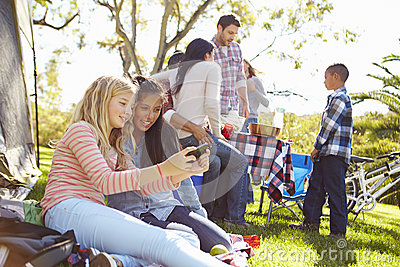 Two Girls Using Mobile Phone On Family Camping Holiday