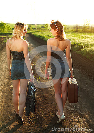 Two girls walking along the road at sunset