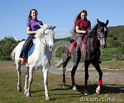Two girls walking on horseback