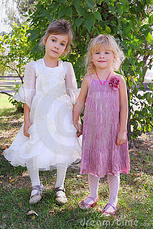 Two girls wearing beautiful dresses holding hands