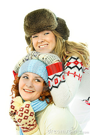 Two girls wearing warm winter clothes have fun