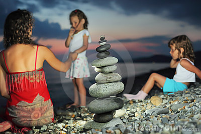 Two girls and woman sitting on stone seacoast