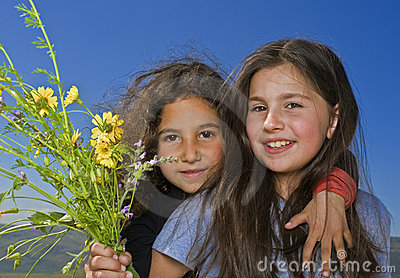 Two girls and yellow flowers