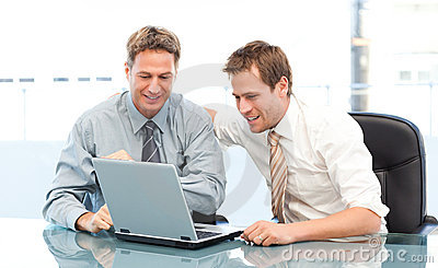 Two glad businessmen working together on a laptop
