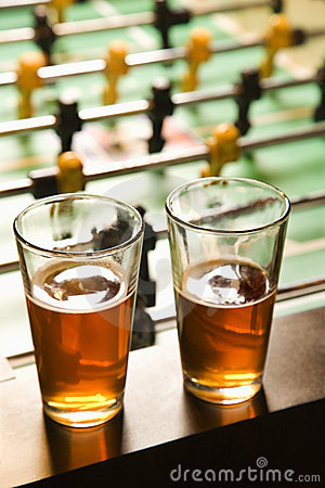 Two glasses of beer at football table.