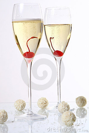 Two glasses with champagne and desert cherry