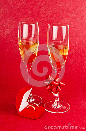 Two glasses with champagne and jewelry box on red