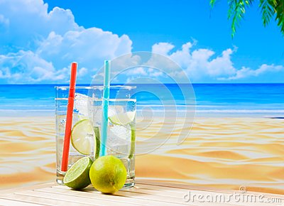 Two glasses of cocktail with lime slice on blur beach and palm