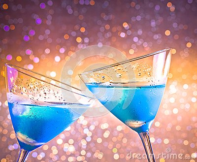 Two glasses of  fresh blue cocktail with ice make cheers