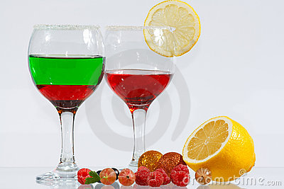 Two glasses of liquor, lemon and berries
