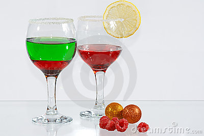 Two glasses of liquor, lemon and raspberries