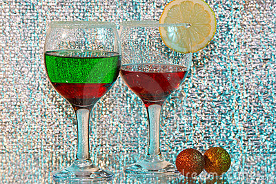 Two glasses of red and green liquor and lemon