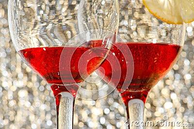 Two glasses of red liquor and lemon