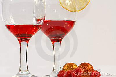 Two glasses of red liquor, lemon and raspberries