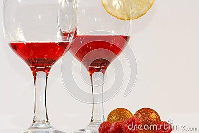 Two glasses of red liquor, lemon and raspberries