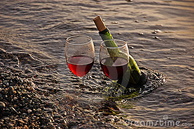 Two Glasses Red Wine and Bottle in Ocean
