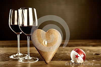 Two glasses of red wine, gingerbread and christmas baubel