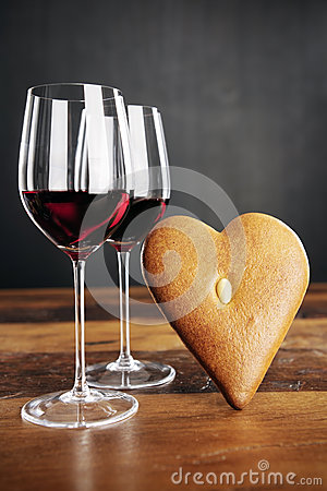 Two glasses of red wine and heart-shaped gingerbread