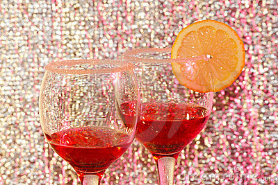 Two glasses of transparent red liquor and lemon