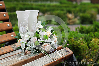 Two glasses and wedding bouquet on a bench