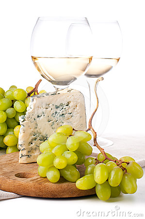 Two glasses of white wine, cheese and a grapes