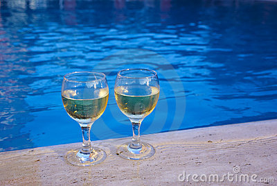 Two glasses with wine at the poolside