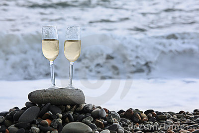 Two glasses of wine on stony beach