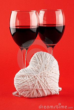 Two glasses of wine and a white heart made of wool