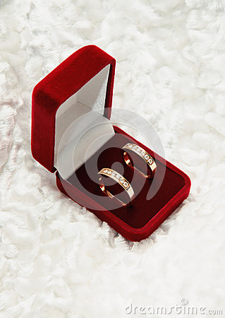 Two gold diamond rings in open box. Love symbol