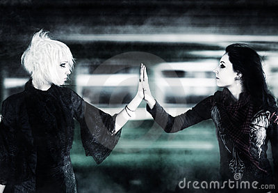 Two goth women touching hands