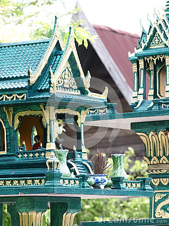 Two green spirit house in thailand with flower vases