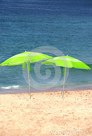 Two green sun umbrellas on the beach