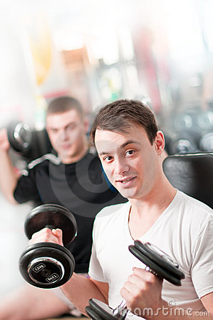 Two guys lifting heavy dumbbells