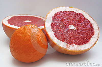Two halfs of red grape fruit and an orange