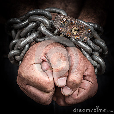 Two hands chained with an iron chain and a padlock