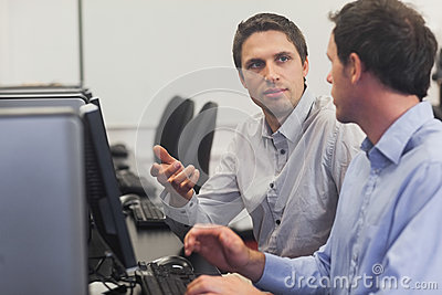 Two handsome men talking while sitting in computer class