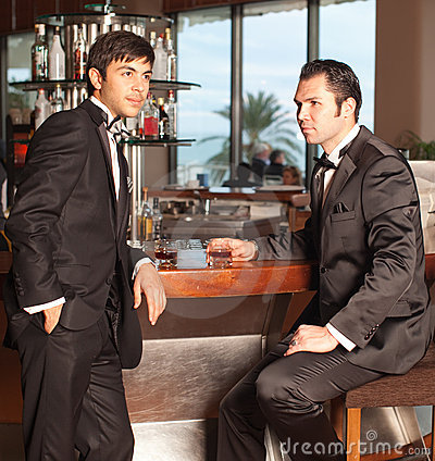 Two handsome men in tuxedo at bar holding whisky