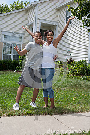 Two Happy African American Home Owners in front of House