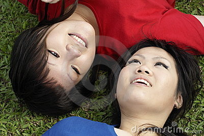 Two happy asian girls on grass