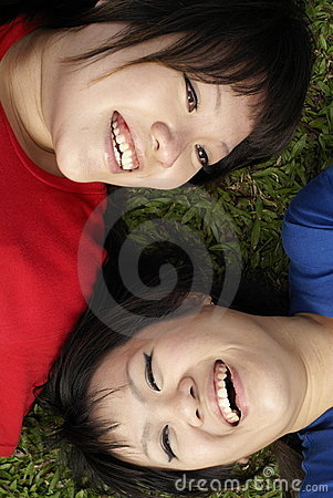 Two happy asian teen girls laughing