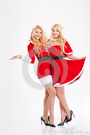 Free Two Happy Beautiful Sisters Twins Hugging  In Santa Claus Costumes Stock Photography - 63506282