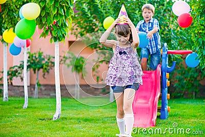 Two happy children sliding at playground